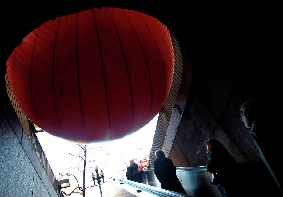 Commuters gaze at a 15-foot inflatable ball wedged into a stairway at the Embarcadero BART station in San Francisco, Calif. on Tuesday, April 9, 2013. Artist Kurt Perschke brought his Red Ball Project art installation to the station for the day to entertain and amuse commuters as they arrived and departed. Photo: Paul Chinn, The Chronicle / ONLINE_YES
