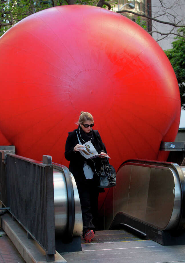 A woman appears unaware of a 15-foot inflatable ball as she leaves the Embarcadero BART station in San Francisco, Calif. on Tuesday, April 9, 2013. Artist Kurt Perschke brought his Red Ball Project art installation to the station for the day to entertain and amuse commuters as they arrived and departed. Photo: Paul Chinn, The Chronicle / ONLINE_YES