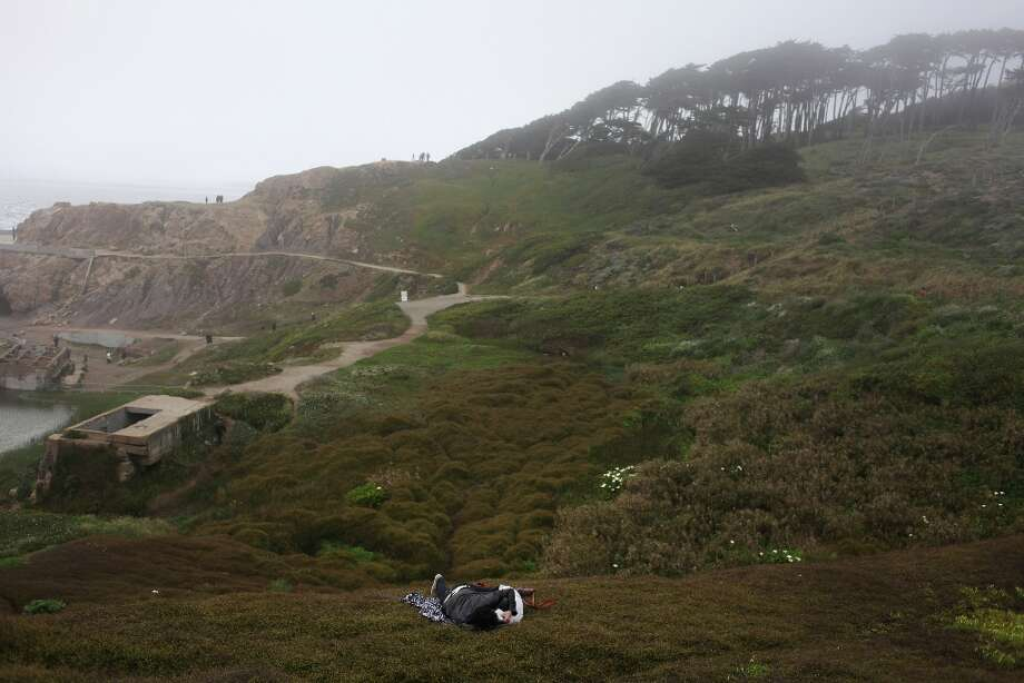 A couple lies just off the trail above Sutro Baths, just across Point Lobos Ave. from Sutro Heights, on April 2, 2013 in San Francisco, Calif. Photo: Pete Kiehart, The Chronicle / ONLINE_YES