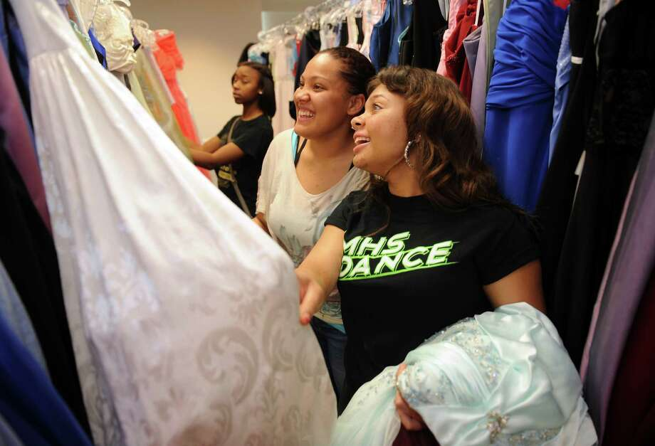 Cy-Lakes senior Michelle Catman, left, and Cy-Woods sophomore Chai Kyham pick out dresses during the ninth annual Prom Dress Give-Away at Lone Star College Cy-Fair Library. The dresses are free and theirs to keep. Photo: Thomas Nguyen, Freelance / Freelance