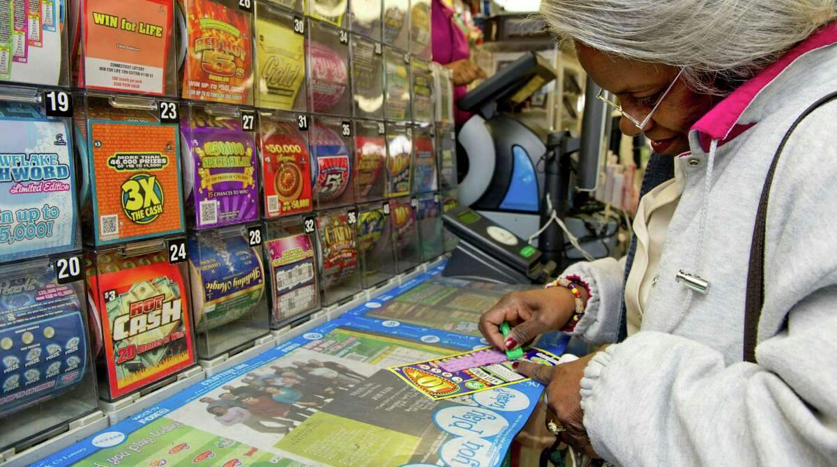 A lottery ticket is scratched off by Gwen Grimes at One Stop Variety in Norwalk, Conn., on Saturday, April 6, 2013.