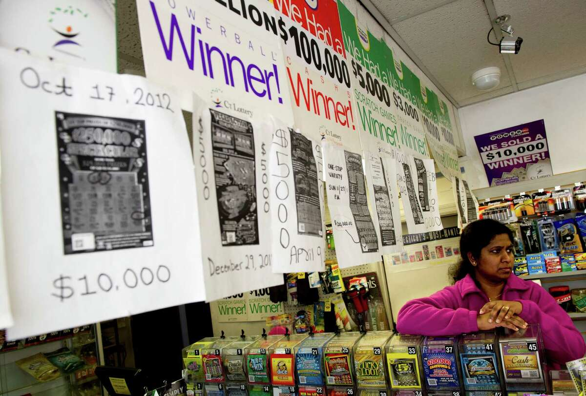 Employee Ganga Fernando stands behind the lottery tickets where posters announcing all the lottery winners hang at One Stop Variety in Norwalk, Conn., on Saturday, April 6, 2013.