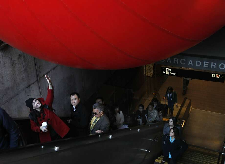 Isabel Archer reaches out to touch a 15-foot inflatable ball wedged into a stairway at the Embarcadero BART station in San Francisco, Calif. on Tuesday, April 9, 2013. Artist Kurt Perschke brought his Red Ball Project art installation to the station for the day to entertain and amuse commuters as they arrived and departed. Photo: Paul Chinn, The Chronicle