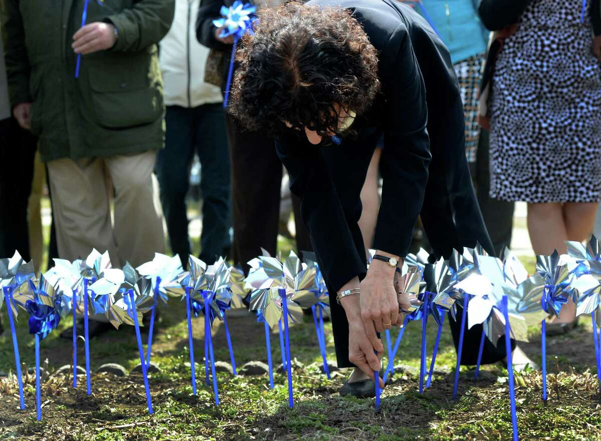 Janice Molnar of the state Office of Children and Family Services, plants a pinwheelin the Pinwheels for Prevention Garden at Huyck Square Monday afternoon April 9, 2013, in Rensselaer, N.Y. Pinwheels for Prevention is the name of the program that donates funds to the prevention of child abuse. (Skip Dickstein/Times Union)
