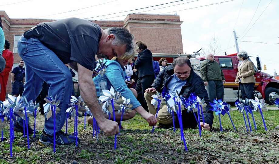 Workers at the state Office of Children and Family Services plant pinwheels in the Pinwheels for Prevention Garden at Huyck Square Monday afternoon April 9, 2013,  in Rensselaer, N.Y.  Pinwheels for Prevention is the name of the program that donates funds to the prevention of child abuse.   (Skip Dickstein/Times Union) Photo: SKIP DICKSTEIN / 10021908A