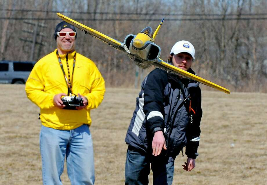 Dan Innes, right, launches an electric motor Parkzone Habu model airplane as Brian McNamara uses the controller to fly the aircraft at Gratwick Park in North Tonawanda, N.Y., on Saturday, April 6, 2013. (AP Photo/Tonawanda News, Don Heupel) Photo: Don Heupel, Associated Press