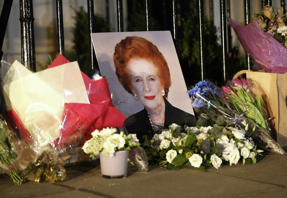 "Flowers placed by mourners surround a portrait of former British Prime Minister Margaret Thatcher outside her home in Belgravia, London, after news of her death came Monday.  The combative ""Iron Lady""  was 87 years old. Photo: Sang Tan / Associated Press"