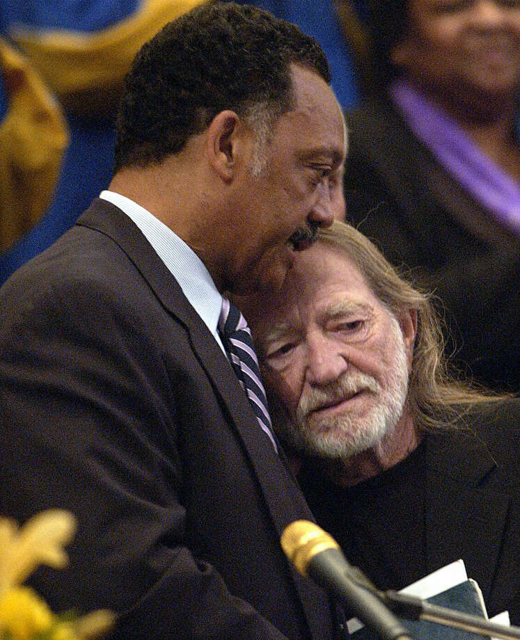 "LOS ANGELES, UNITED STATES:  The Rev. Jesse Jackson (L) and singer Willie Nelson attend the funeral of legendary singer and musician Ray Charles at his funeral at the First AME Church in Los Angeles 18 June 2004. Charles, who was known as ""the Genius of Soul,"" died last week of liver disease at age 73. AFP PHOTO / POOL / Reed SAXON Photo: AFP, Getty / 2004 AFP"