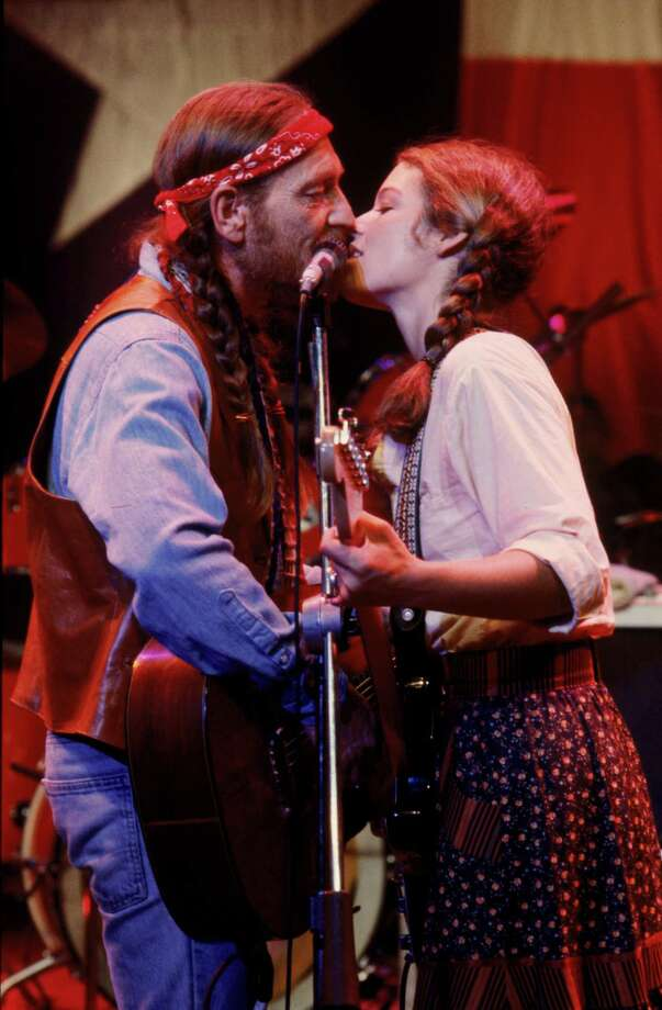 UNSPECIFIED - DECEMBER 11:  Medium profile shot of Willie Nelson as Buck, wearing headband/bandana, and Amy Irving as Lily; both holding guitars and singing into same microphone. Photo: Warner Bros., Getty / (C) Warner Bros. Entertainment Inc.