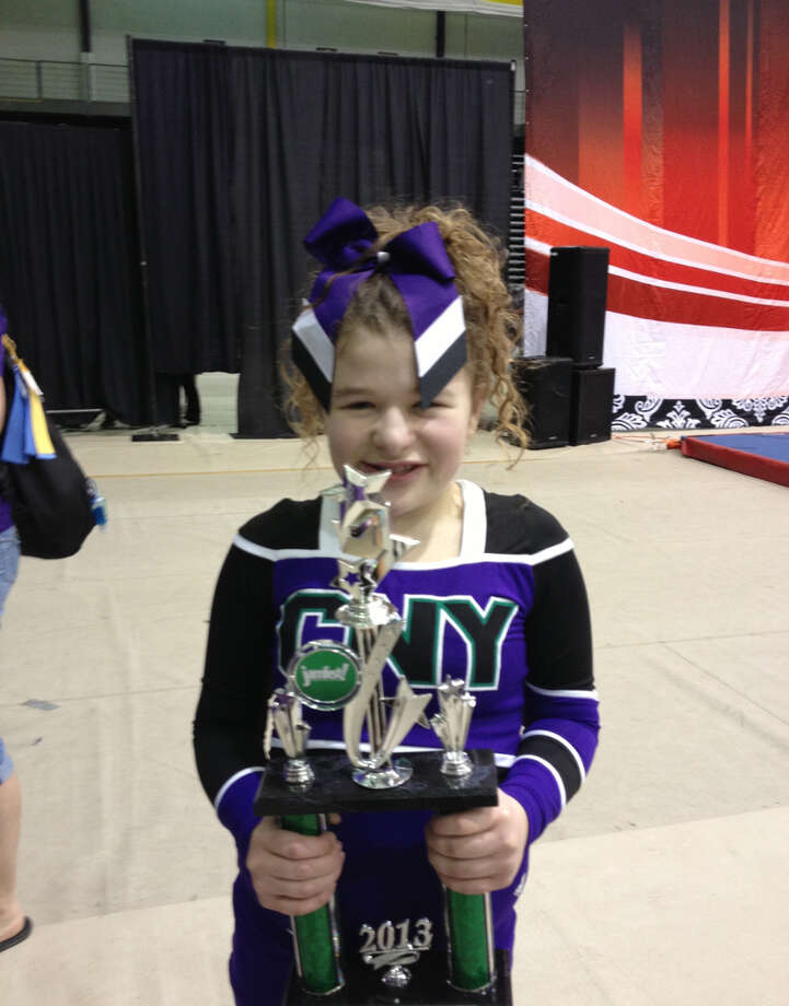 Francesca Betz, 12, of Clifton Park shows off a trophy awarded to the CNY Rainbows cheer team, at the Spirit Unlimited competition on Saturday, April 6, 2013, at University at Albany in Albany, N.Y. (Photo Courtesy Of Kelly Betz)
