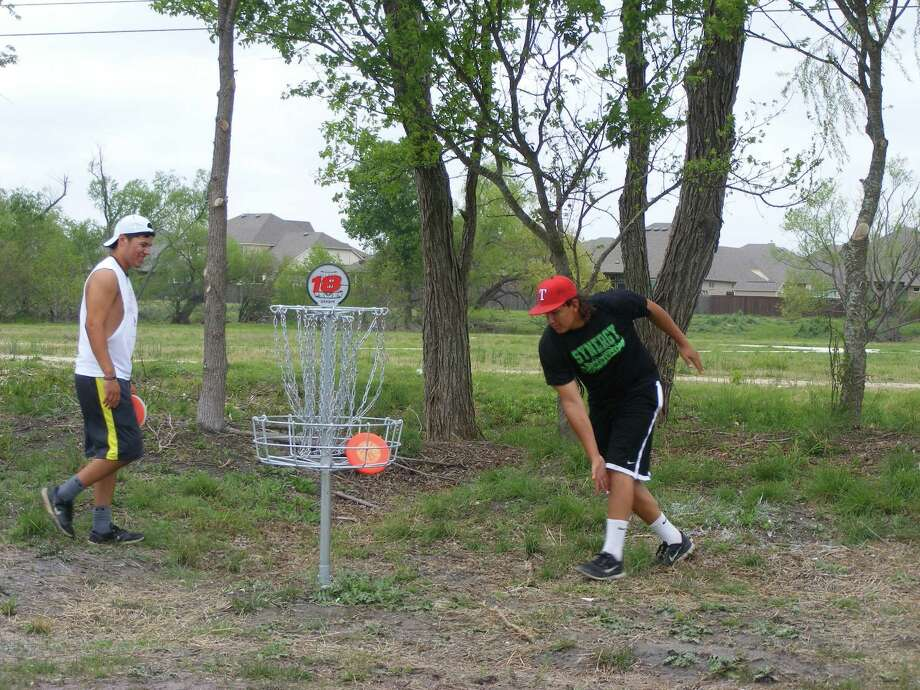 "Trevor Ahin (left) watches Sunday as Cash Miller drops a ""putt"" into a basket on the new Cibolo disc golf course at Schlather Park. Photo: David DeKunder / NE Herald"