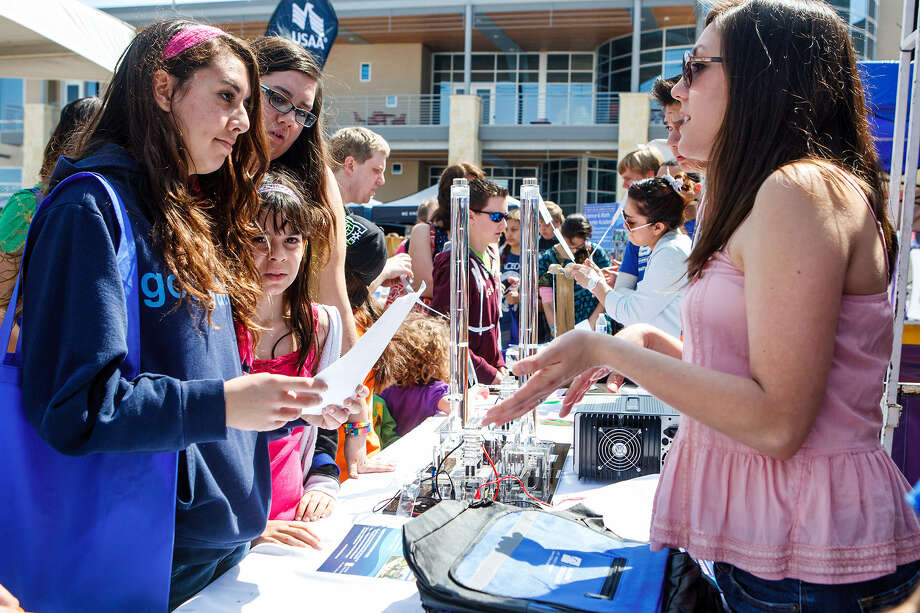 Audrie Cabrera (right), with St. Philip's College, talks to (from left) Cianna Garcia, 15, Serena Garcia, 8, and Lysandra Garcia, 16, about the school's STEM – Science, Technology, Engineering and Mathematics -- program during the Girls Inc. of San Antonio's 7th annual RockIt into The Future Science Festival Saturday, presented by Rackspace Hosting in Windcrest. Photo: Marvin Pfeiffer / NE Herald