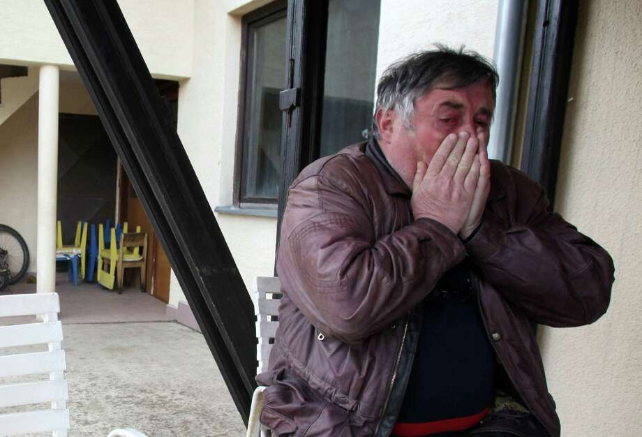 Radmilo Bogdanovic, brother of the suspect, reacts in horror Tuesday to news of the slayings. Photo: Darko Vojinovic, STF / AP