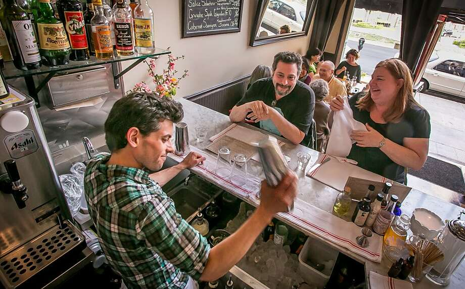 Bartender Zach Miller, above, shakes a cocktail for Rachel Warner and Lee Greenberg at Hopscotch, which features such sandwiches as the First Base Burger with beef tongue, right, and such drinks as the Maple Old Fashioned with rye and maple syrup, far right. Photo: John Storey, Special To The Chronicle
