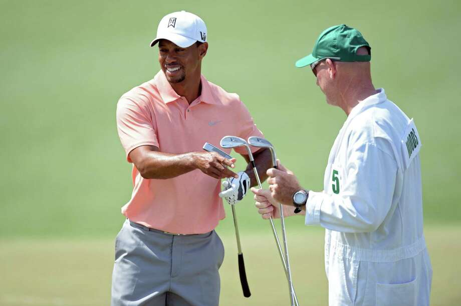 Tiger Woods takes a club from his caddie, Joe LeCava, during a practice round Tuesday at Augusta. Photo: Harry How / Getty Images