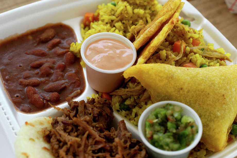 This is a SAbores plate at the food truck Sabor Colombiano. The plate is a sampler and provides beans (upper left), arepa with carne (bottom left), an empanada (right), rice with chicken (below empanada) and tostones (fried plantains, nestled in rice). Photo: JOHN DAVENPORT, SAN ANTONIO EXPRESS-NEWS / ©San Antonio Express-News/Photo may be sold to the public