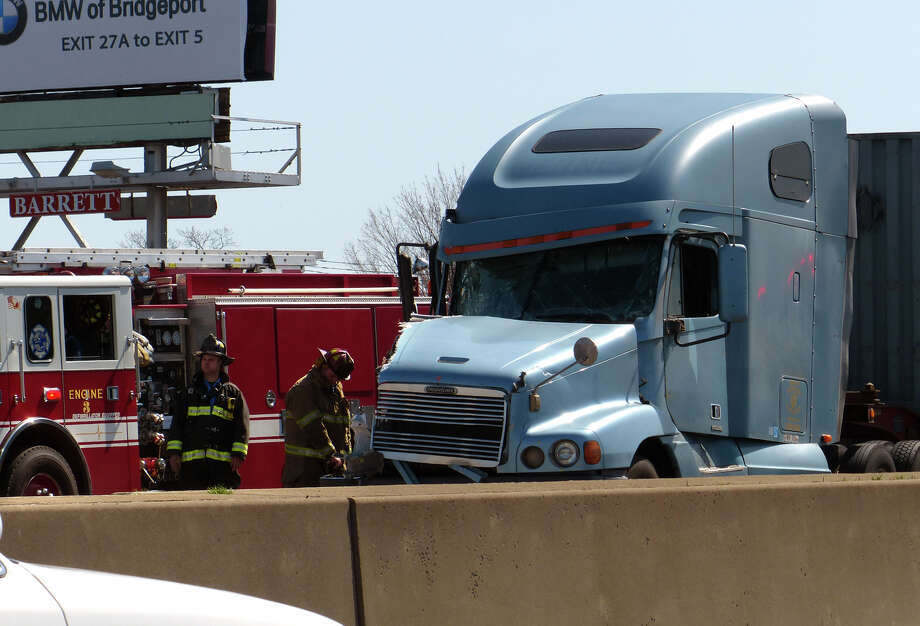 Stratford firefighters standby at the scene of an accident involving a tractor trailer in the northbound lanes of I95 in Stratford, Conn. on Tuesday April 9, 2013. All of the lanes were blocked causing traffic to back up for miles. Photo: Christian Abraham