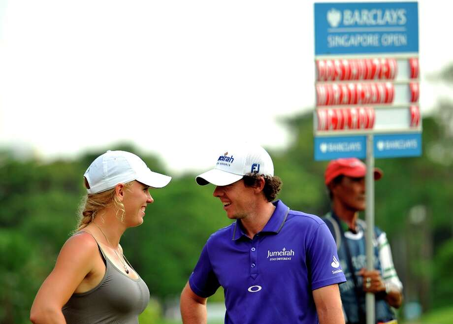 This handout photo provided by World Sport Group on November 10, 2012, shows Rory McIlroy of Ireland and his girlfriend, tennis player, Caroline Wozniacki of Denmark during day three of the Barclays Singapore Open Golf tournament at the Sentosa Golf Club in Singapore.  The six million USD event, co-sanctioned by the European and Asian Tours, runs from November 8 to 11. Photo: PAUL LAKATOS, AFP/Getty Images / 2012 AFP