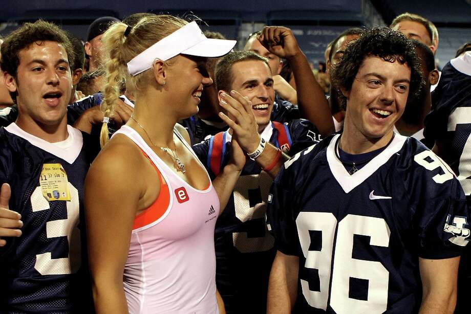 Caroline Wozniacki of Denmark and golfer Rory McIlroy of Northern Ireland meet members of the Yale football team after her win over Francesca Shiavone of Italy during the semifinals of the New Haven Open at Yale presented by First Niagara at the Connecticut Tennis Center on August 26, 2011 in New Haven, Connecticut. Photo: Matthew Stockman, Getty Images / 2011 Getty Images