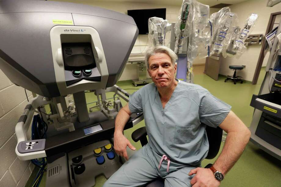 In this March 22, 2013 photo, Dr. Pier Giulianotti, chief of minimally invasive and robotic surgery at the University of Illinois Hospital & Health Sciences System in Chicago, sits at the control panel of the da Vinci robot system. Surgeons say the advantages of the system include allowing them to operate sitting down, using small robotic hands with no tremor. But critics say a big increase in robot operations nationwide is due to heavy marketing and hype, and the U.S. Food and Drug Administration is looking into problems and deaths that may be linked with robotic surgery. (AP Photo/M. Spencer Green) Photo: M. Spencer Green, STF / AP