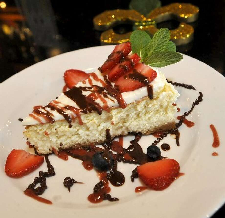 This desert is a classic piece of cheesecake with strawberries, and blueberries and covered with chocolate and strawberry icings.