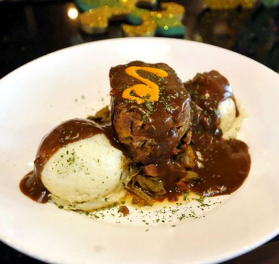 A meat loaf dish with garlic mashed potatoes and brazed greens.