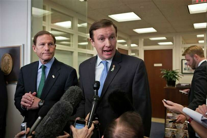 Sen. Chris Murphy, D-Conn., right, accompanied by Sen. Richard Blumenthal, D-Conn., speaks to report