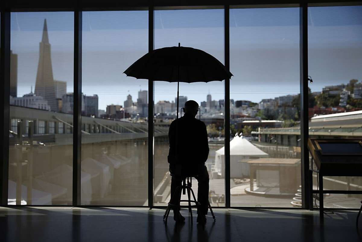 Bryan Connell, exhibit developer, sits at the Surveying in the City exhibit behind fritted glass in the Fisher Bay Observatory Gallery at the new Exploratorium on Tuesday, April 9, 2013 in San Francisco, Calif. Fritted glass helps to reduce the solar gain at the new Exploratorium.