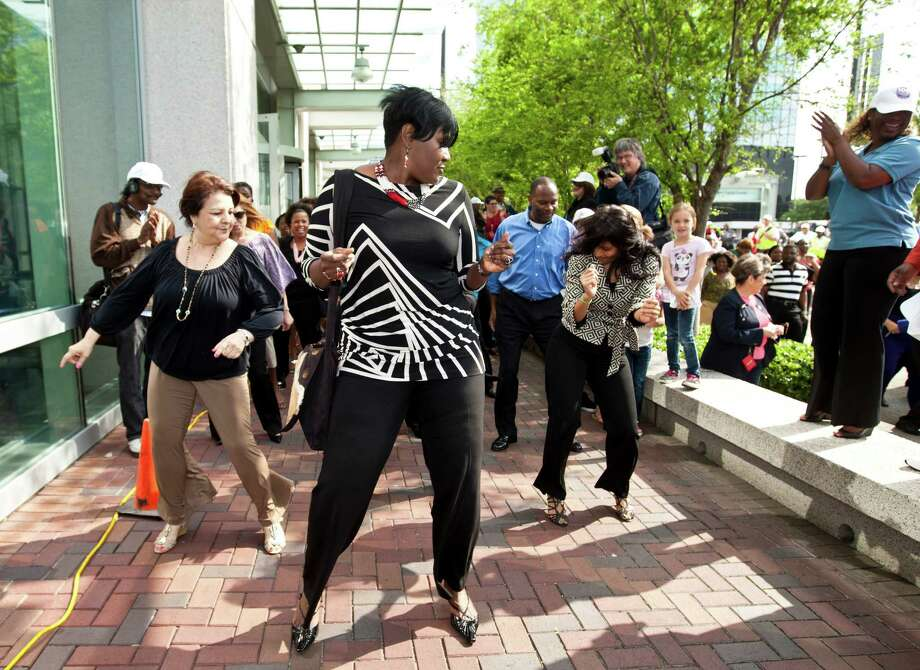 Houston City Councilwoman Wanda Adam, center, participates in a flash mob dance during METRORail's 100 millionth boarding celebration, Tuesday, April 9, 2013, outside METRO's downtown transit center in Houston. Photo: Nick De La Torre, Chronicle / © 2013 Houston Chronicle