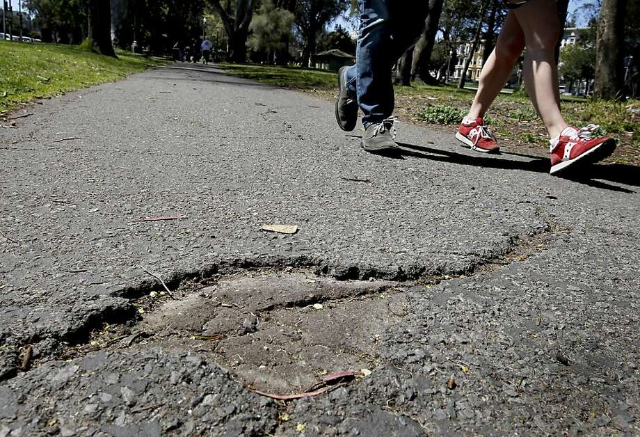 People on the Panhandle's south path try to steer clear of lumpy asphalt. Photo: Brant Ward, The Chronicle