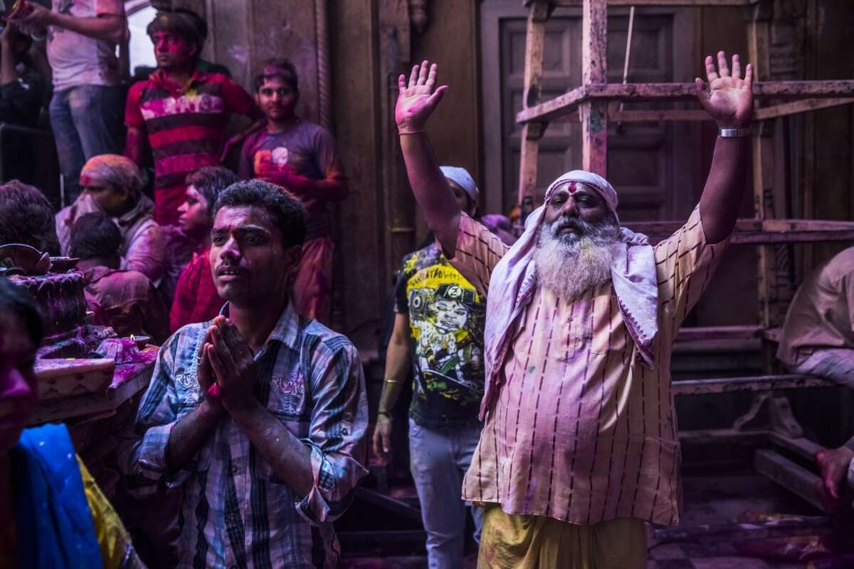 No. 8: Our gods and religions are influential in our lives. Photo: Hindu devotees wait for a statue of Lord Krishna to be revealed during Holi celebrations at the Banke Bihari temple on March 26, 2013 in Vrindavan, India. The tradition of playing with colors on Holi draws its roots from a legend of Radha and the Hindu God Krishna. It is believed that young Krishna was jealous of Radha\'s fair complexion since he himself was very dark. After questioning his mother Yashoda on the darkness of his complexion, Yashoda, teasingly asked him to colour Radha\'s face in which ever color he wanted. In a mischievous mood, Krishna applied colour on Radha\'s face. The tradition of applying color on one\'s beloved is being religiously followed till date. (Photo by Daniel Berehulak/Getty Images)