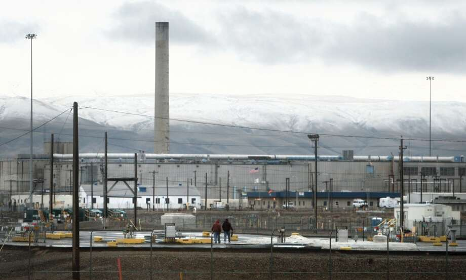 Workers walk on a blacktop covering leaking nuclear waste storage tanks seen during a tour of the Hanford Nuclear Reservation. In recent weeks these tanks have been discovered to be leaking at a rate much higher than previously thought. (Joshua Trujillo, seattlepi.com)