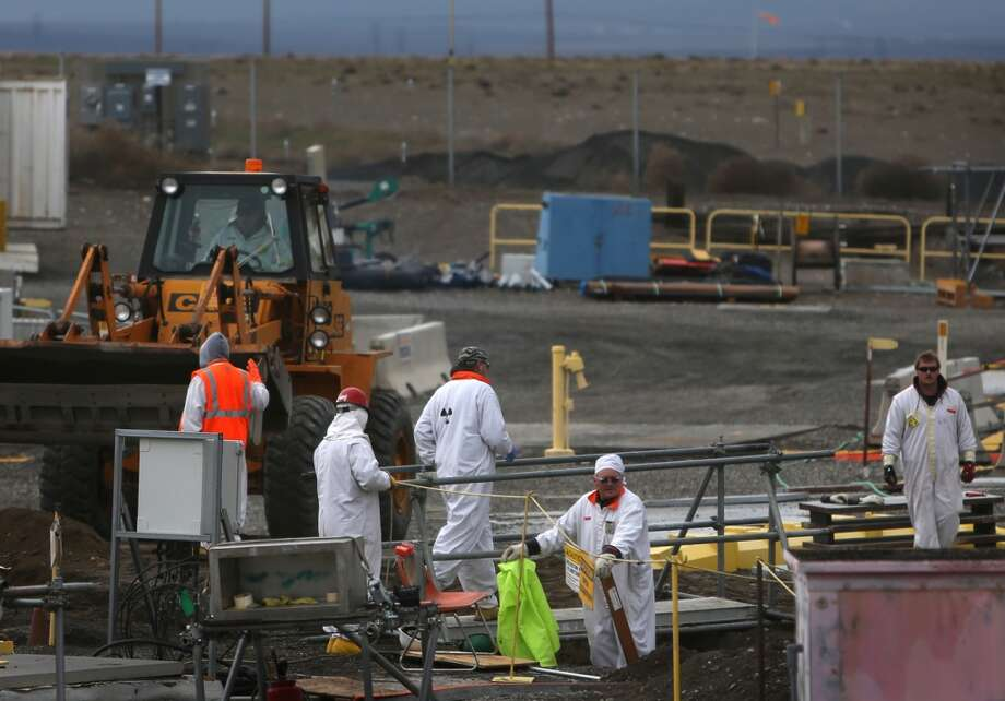 "Workers clean up in a contaminated area of a tank ""farm"" seen during a tour of the Hanford Nuclear Reservation near Richland on Wednesday, March 6, 2013. Tanks holding nuclear waste at the facility have been discovered in recent weeks to be leaking radioactive waste into the ground. The leaks have been discovered to be occurring at a far higher rate than previously believed. (Joshua Trujillo, seattlepi.com)"
