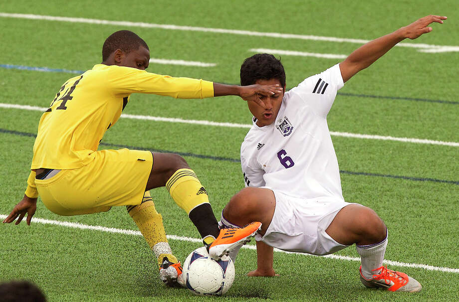 Ridge Point midfielder Luis Penate-Rodriguez (6) tackles Houston Lee's Dunia Mukule (14) during the first half of the Class 4A region soccer quarterfinals at Mercer Stadium on Tuesday, April 9, 2013, in Sugar Land. Photo: J. Patric Schneider, For The Chronicle / © 2013 Houston Chronicle