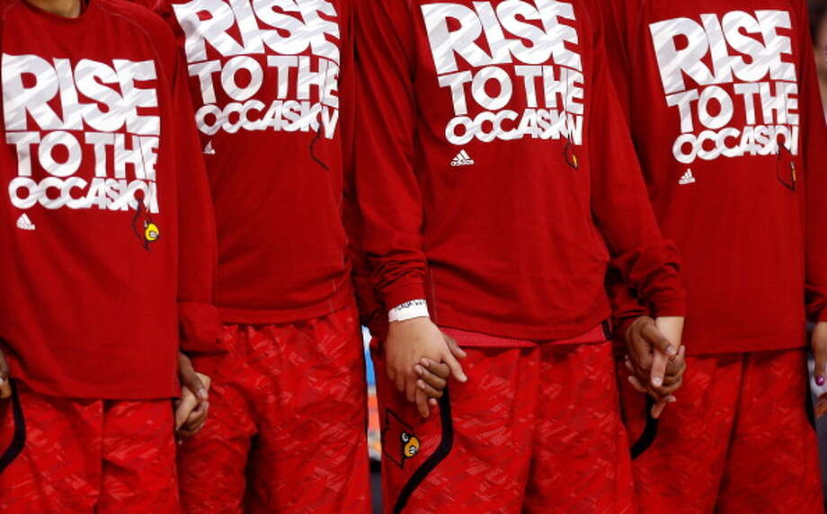 The Louisville Cardinals hold hands and look on during the National Anthem prior to the game against the Connecticut Huskies during the 2013 NCAA Women\'s Final Four Championship at New Orleans Arena on April 9, 2013 in New Orleans, Louisiana. Photo: Chris Graythen, Getty Images / 2013 Getty Images