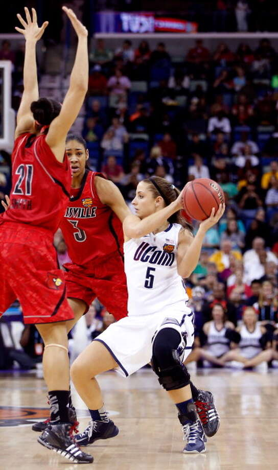 Caroline Doty #5 of the Connecticut Huskies looks to pass against Bria Smith #21 and Sheronne Vails #3 of the Louisville Cardinals in the first half during the 2013 NCAA Women\'s Final Four Championship at New Orleans Arena on April 9, 2013 in New Orleans, Louisiana. Photo: Chris Graythen, Getty Images / 2013 Getty Images