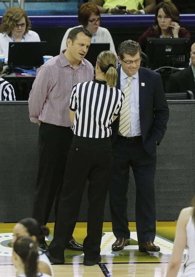 Louisville head coach Jeff Walz, left and Connecticut head coach Geno Auriemma speaks to an official about a foul during first half of the national championship game of the women\'s Final Four of the NCAA college basketball tournament, Tuesday, April 9, 2013, in New Orleans.