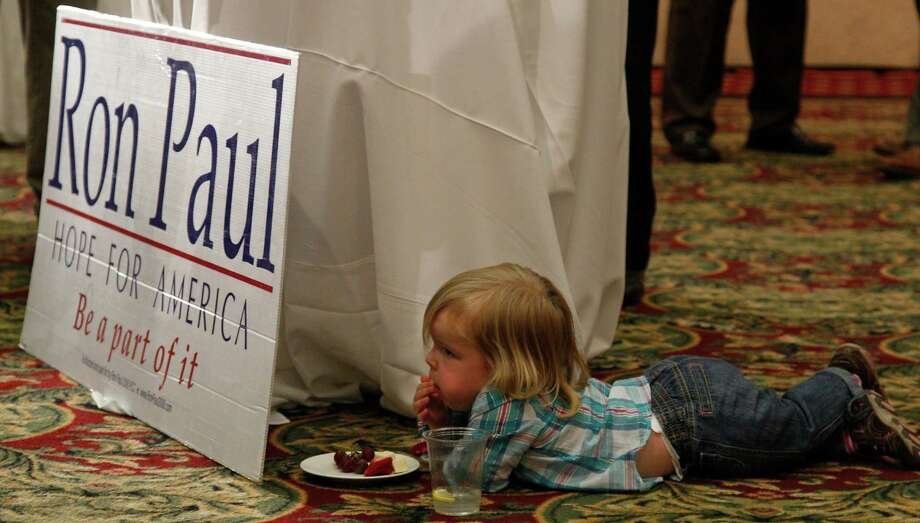 Eisley Collins, 2, snacks next to a Ron Paul sign at a Republican watch party in Oklahoma City, Tuesday, March 6, 2012. Photo: Sue Ogrocki, Associated Press / AP