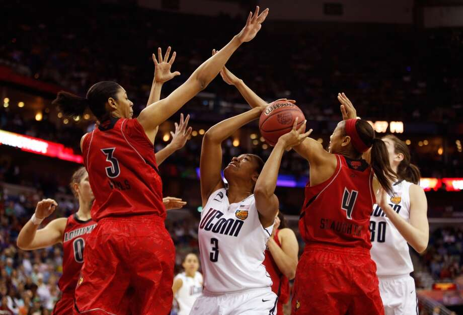 Morgan Tuck #3 of the Connecticut Huskies handles the ball under the basket against Sheronne Vails #3 and Antonita Slaughter #4 of the Louisville Cardinals in the first half during the 2013 NCAA Women\'s Final Four Championship at New Orleans Arena on April 9, 2013 in New Orleans, Louisiana.