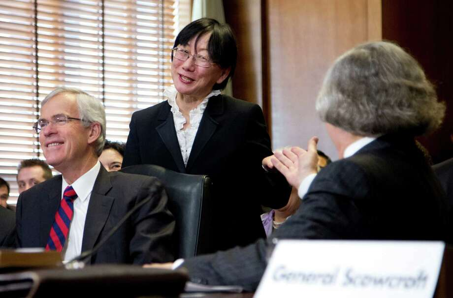 Naomi Moniz, center, wife of Energy Secretary nominee Ernest Moniz, right, acknowledges her husband as she is introduced on Capitol Hill in Washington, Tuesday, April 9, 2013, during the Senate Energy and Natural Resources Committee hearing Moniz's nomination. At left is former New Mexico Sen. Jeff Bingaman, a former chairman of the committee who helped in introducing Moniz to the committee.  (AP Photo/Manuel Balce Ceneta) Photo: Manuel Balce Ceneta, STF / AP