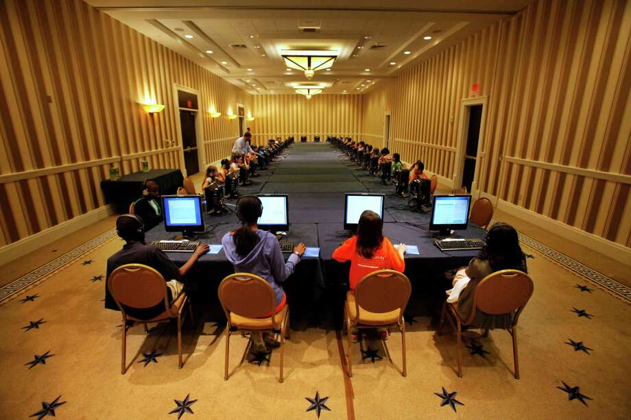 FILE - In this May 29, 2012 file photo, contestants in the National Spelling Bee take the written exam on computers in Oxon Hill, Md., before the oral competition began. Ever wonder if those spelling bee kids know the meanings of some of those big words? Now they'll have to prove that they do. Organizers of the Scripps National Spelling Bee on Tuesday announced a major change to the format, adding multiple-choice vocabulary tests to the annual competition that crowns the English language's spelling champ. (AP Photo/Jacquelyn Martin, File) Photo: Jacquelyn Martin