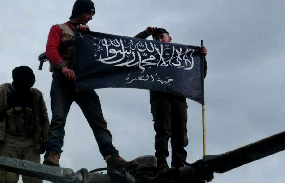 """FILE - In this Friday, Jan. 11, 2013 file citizen journalism image provided by Edlib News Network, ENN, which has been authenticated based on its contents and other AP reporting, shows rebels from al-Qaida affiliated Jabhat al-Nusra waving their brigade flag on the top of a Syrian air force helicopter, at Taftanaz air base that was captured by the rebels, in Idlib province, northern Syria.  Al-Qaida's branch in Iraq said it has merged with Syria's extremist Jabhat al-Nusra, a move that shows the rising confidence of radicals within the Syrian rebel movement and is likely to trigger renewed fears among its international backers. Arabic on the flag reads, """"There is no God only God and Mohamad his prophet, Jabhat al-Nusra."""" (AP Photo/Edlib News Network ENN, File) Photo: Anonymous"""