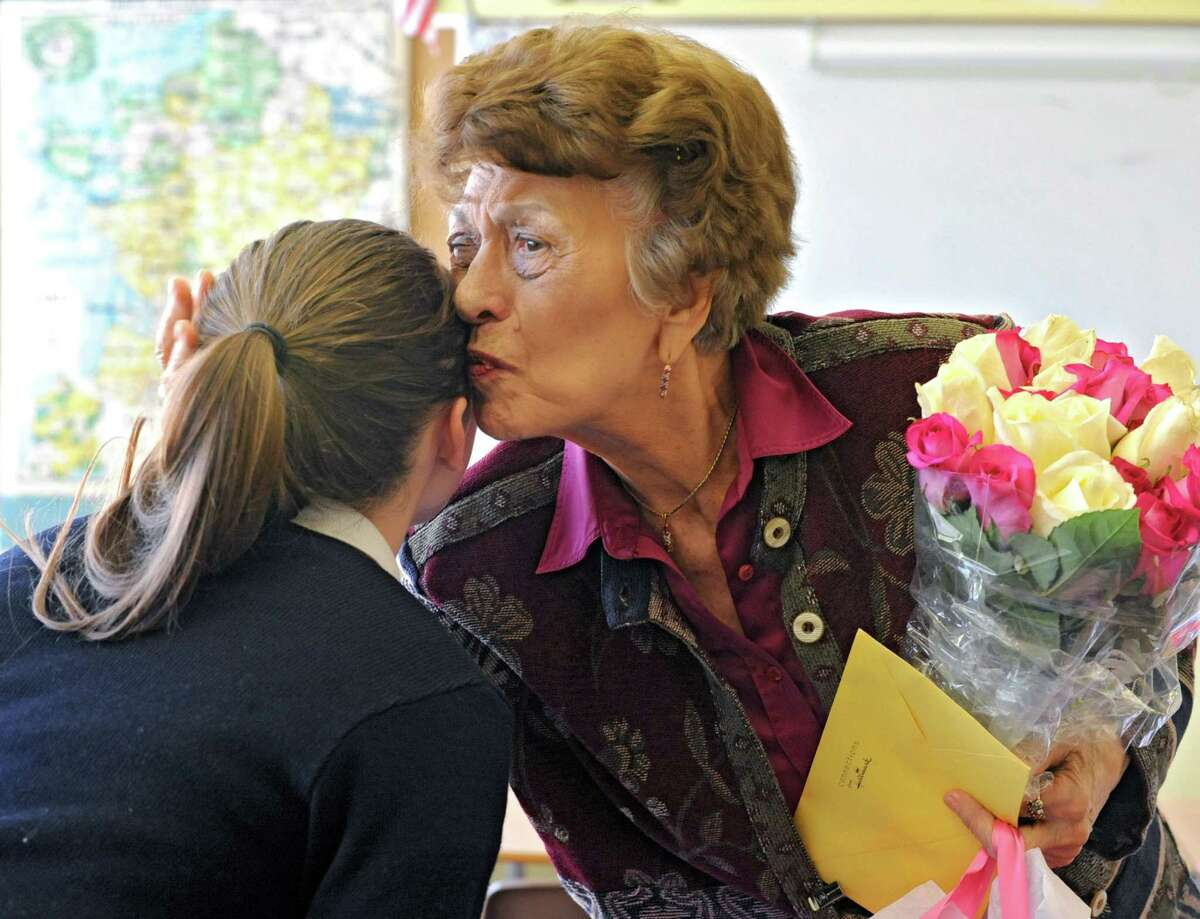 Ninety-year-old teacher Germaine Graf kisses junior Regan Edwards on the head after receiving flowers for her birthday from her advanced french class at Academy of the Holy Names school on Tuesday, April 9, 2013 in Albany, N.Y. Graf has announced she'll retire at the end of this year. (Lori Van Buren / Times Union)