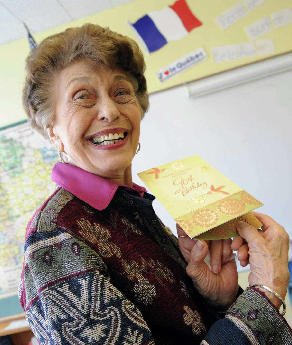 Ninety-year-old french teacher Germaine Graf kisses junior Regan Edwards smiles after opening up a birthday card from her advanced french class at Academy of the Holy Names school on Tuesday, April 9, 2013 in Albany, N.Y. Graf has announced she'll retire at the end of this year. (Lori Van Buren / Times Union)