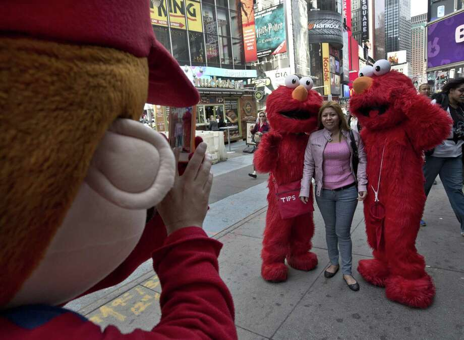 A Super Mario character, left, uses a woman's mobile phone camera to photographer her with a pair of Elmo characters in New York's Times Square,  Tuesday, April 9, 2013. A string of arrests in the last few months has brought unwelcome attention to the growing number of people, mostly poor immigrants, who make a living by donning character outfits, roaming Times Square and charging tourists a few dollars to pose with them in photos. (AP Photo/Richard Drew) Photo: Richard Drew