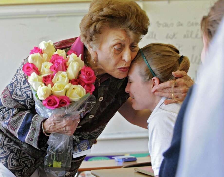 Ninety-year-old french teacher Germaine Graf kisses junior Grace Cummings on the head after receiving flowers for her birthday from her advanced french class at Academy of the Holy Names school on Tuesday, April 9, 2013 in Albany, N.Y. Graf has announced she'll retire at the end of this year. (Lori Van Buren / Times Union) Photo: Lori Van Buren