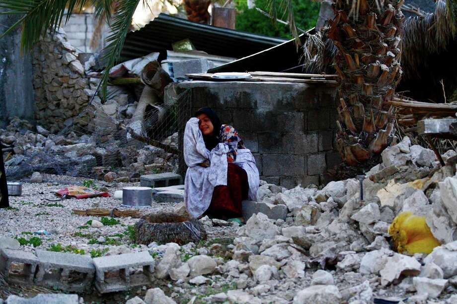 An Iranian woman reacts as she sits among the rubble of buildings after an earthquake struck southern Iran, in Shonbeh, Iran, Tuesday, April 9, 2013. A 6.1 magnitude earthquake killed dozens of people and injured hundreds more in a sparsely populated area in southern Iran on Tuesday, Iranian officials said, adding that it did not damage a nuclear plant in the region. (AP Photo/Fars News Agency, Mohammad Fatemi) Photo: Mohammad Fatemi