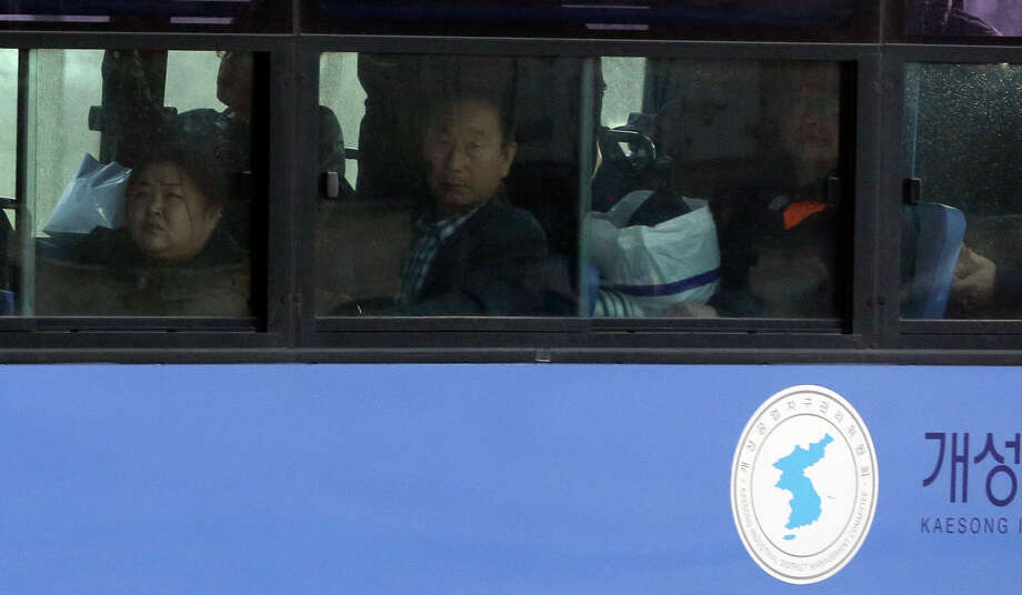 South Koreans look out a bus window upon their arrival from North Korea's Kaesong at the customs, immigration and quarantine office near the border village of Panmunjom, which has separated the two Koreas since the Korean War, in Paju, north of Seoul, South Korea, Tuesday, April 9, 2013. A few hundred South Korean managers, some wandering among quiet assembly lines, were all that remained Tuesday at the massive industrial park run by the rival Koreas after North Korea pulled its more than 50,000 workers from the complex. Others stuffed their cars full of goods before heading south across the Demilitarized Zone that divides the nations. (AP Photo/Lee Jin-man) Photo: Lee Jin-man