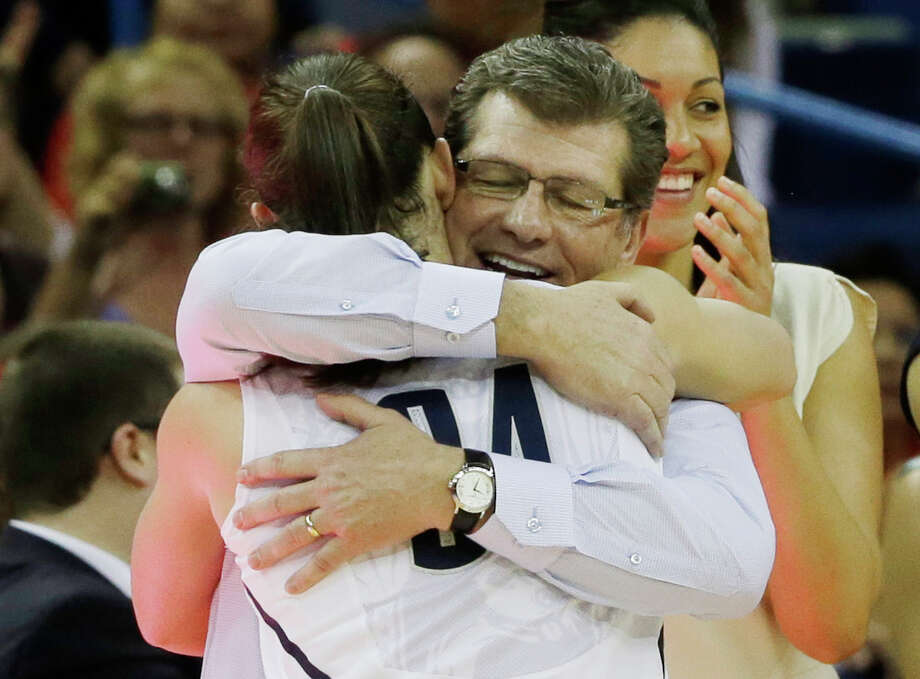 Connecticut head coach Geno Auriemma hugs Kelly Faris (34) during the second half of the national championship game against Louisville at the women's Final Four of the NCAA college basketball tournament, Tuesday, April 9, 2013, in New Orleans. Connecticut won 93-60. (AP Photo/Dave Martin) Photo: Dave Martin, Associated Press / AP