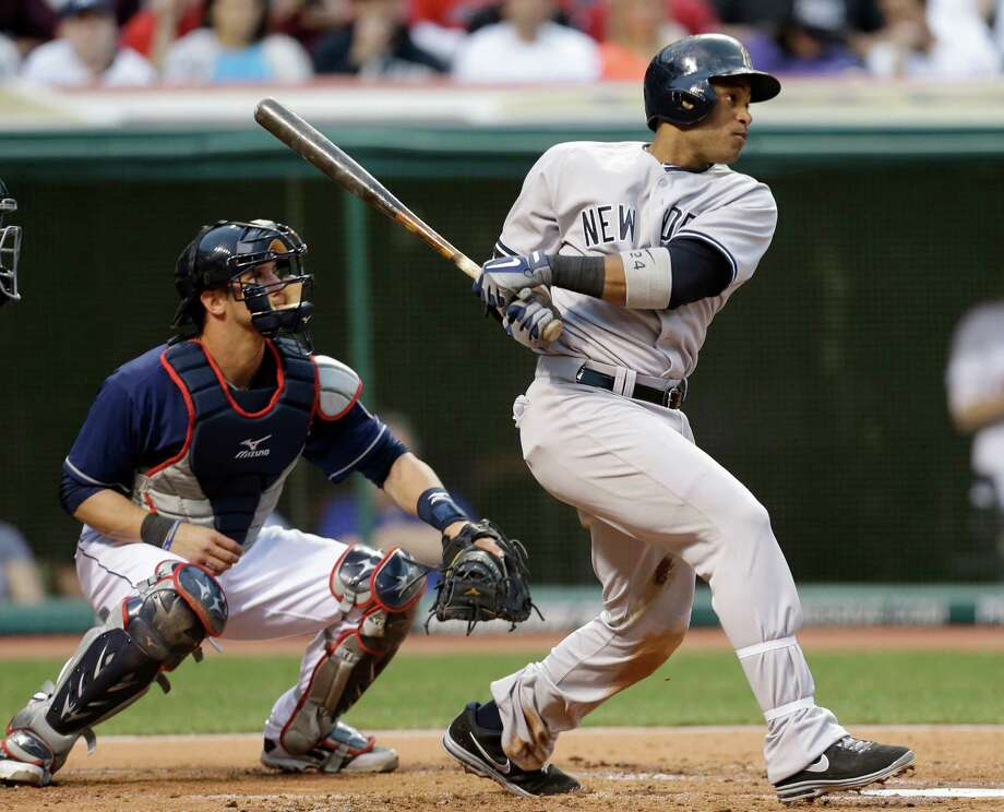 New York Yankees' Robinson Cano watches his two-run double off Cleveland Indians starting pitcher Carlos Carrasco in the second inning of a baseball game, Tuesday, April 9, 2013, in Cleveland. Indians catcher Yan Gomes is at left. (AP Photo/Tony Dejak) Photo: Tony Dejak